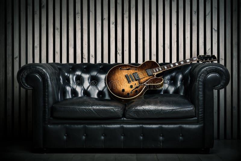 Sofa vide de vintage et guitare électrique avec le fond en bois moderne de studio d'enregistrement de mur Concept de musique avec images stock