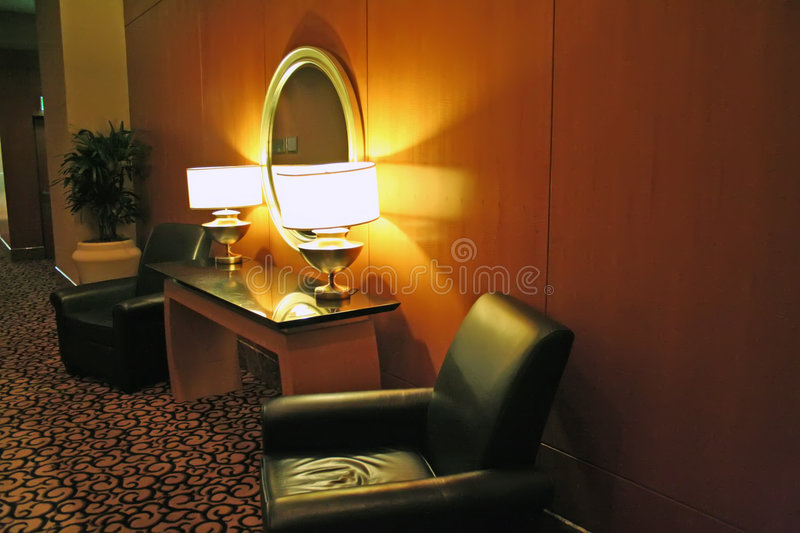 Sofa waiting area. Dimly lit cozy waiting area with leather chairs and lamp royalty free stock image