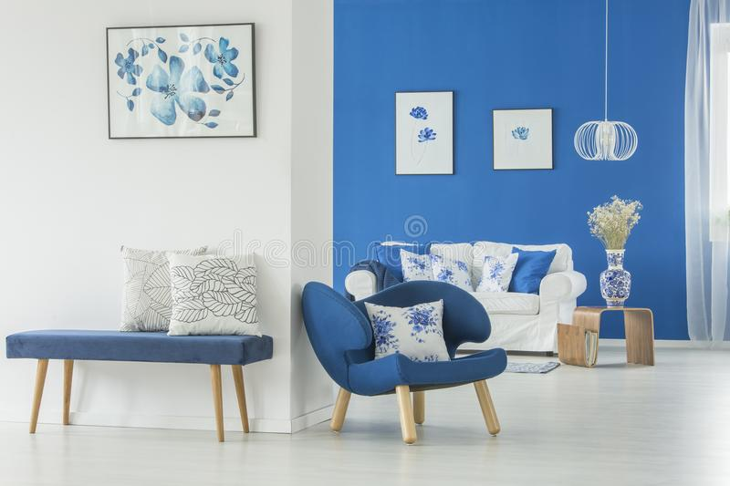 Sofa in white interior. An armchair, bench, sofa and paintings in white and blue themed living room interior royalty free stock image