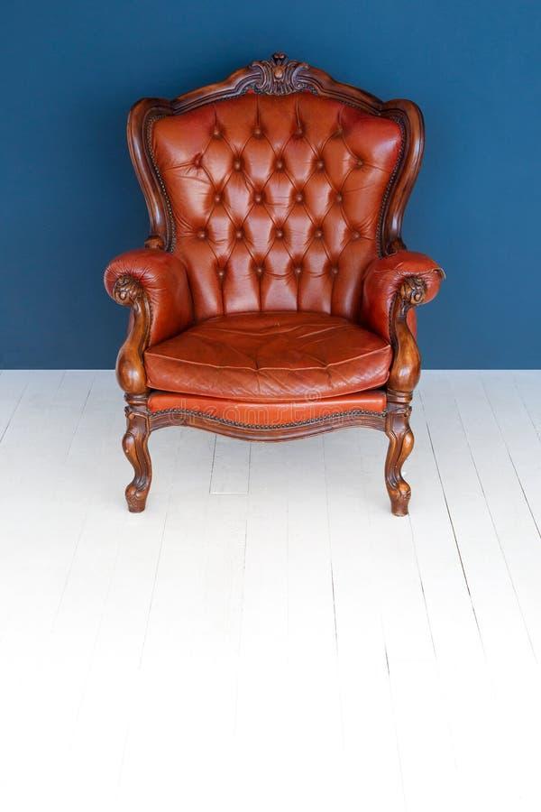 Soffa för läder för brunt för klassiker för fåtölj för brunt för tappningläderlyx och gammal blå bakgrund fotografering för bildbyråer