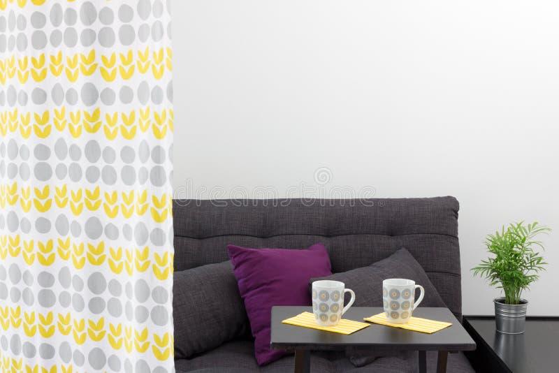 Soffa med kuddar bak en dekorativ gardin arkivbilder