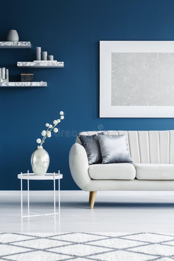 Soffa på den blåa väggen arkivbilder
