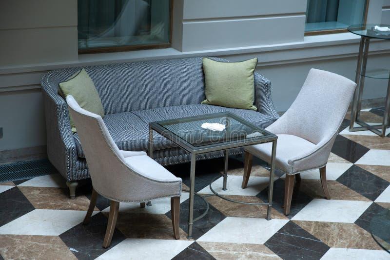 Soffa, två stolar och en tabell i ett rum fotografering för bildbyråer
