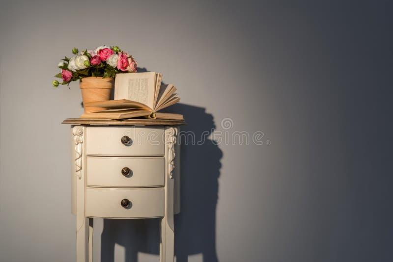 Soffatabell med blommor och boken royaltyfri bild