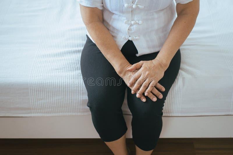 Sofferenza anziana della donna dal dolore nella gamba e nella ferita al ginocchio che si siedono sulla camera da letto immagini stock
