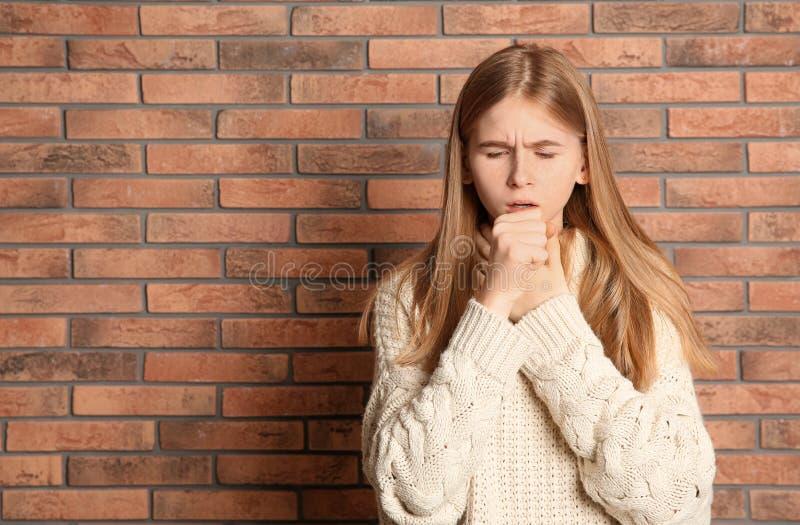 Sofferenza dell'adolescente dalla tosse vicino al muro di mattoni fotografia stock libera da diritti