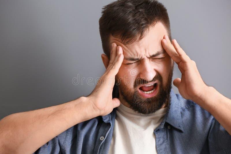 Sofferenza dell'uomo dall'emicrania su fondo grigio fotografia stock libera da diritti