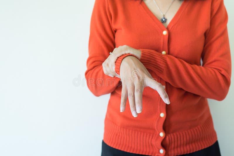 Sofferenza della donna con i sintomi della malattia di parkinson sullo spazio bianco della copia e del fondo fotografia stock