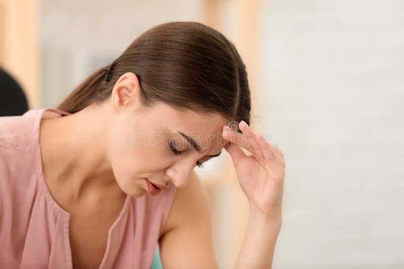 Sofferenza della donna dall'emicrania all'interno immagine stock