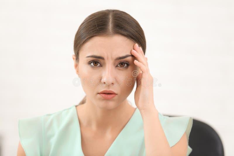 Sofferenza della donna dall'emicrania all'interno fotografie stock