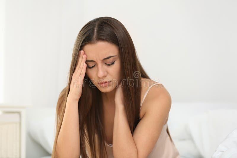 Sofferenza della donna dall'emicrania in camera da letto fotografia stock libera da diritti