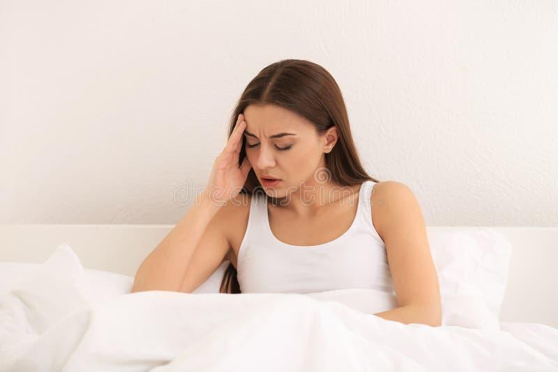 Sofferenza della donna dall'emicrania in camera da letto immagini stock