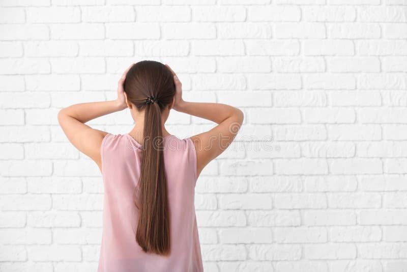 Sofferenza della donna dall'emicrania contro il muro di mattoni bianco immagini stock libere da diritti