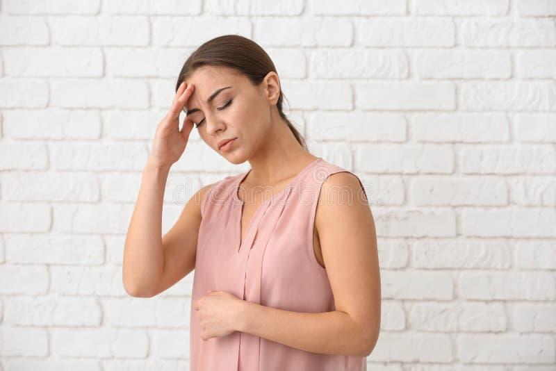 Sofferenza della donna dall'emicrania contro il muro di mattoni bianco fotografia stock