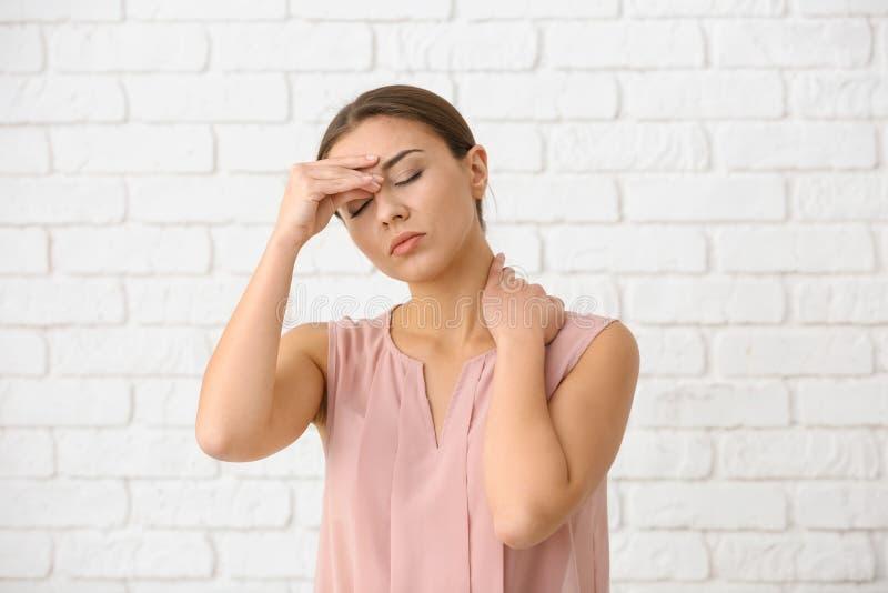 Sofferenza della donna dall'emicrania contro il muro di mattoni bianco fotografie stock