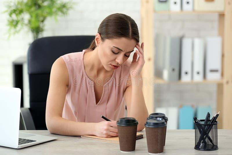 Sofferenza della donna dall'emicrania mentre lavorando nell'ufficio immagini stock