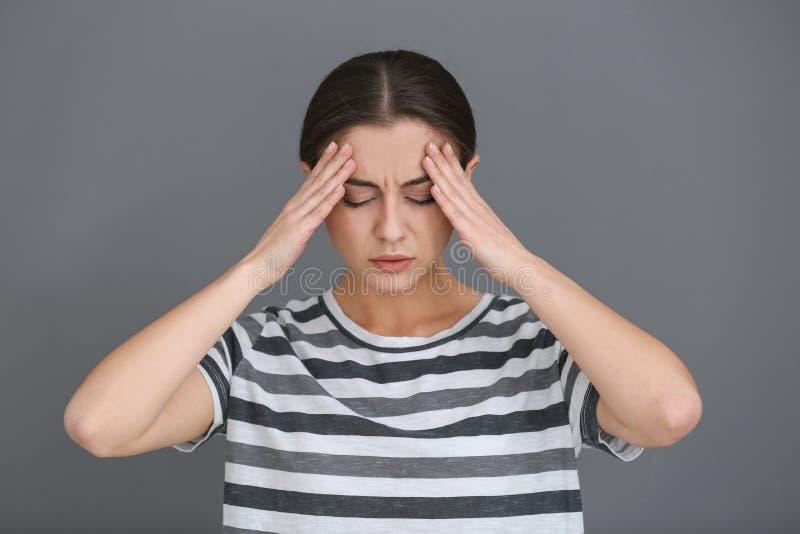 Sofferenza della donna dall'emicrania su fondo grigio fotografia stock