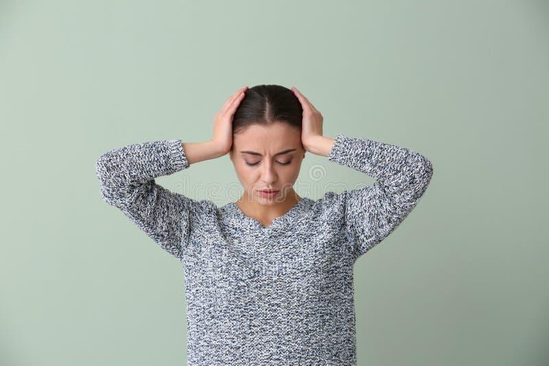 Sofferenza della donna dall'emicrania sul fondo di colore immagini stock libere da diritti