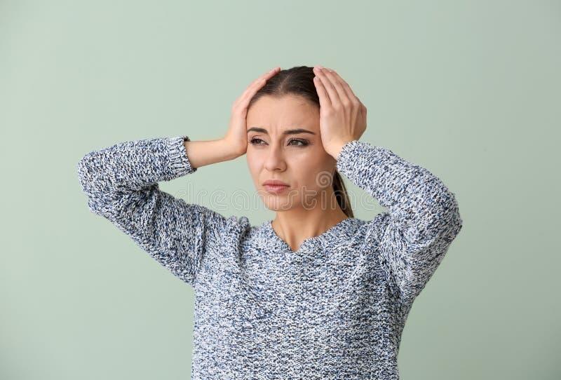 Sofferenza della donna dall'emicrania sul fondo di colore immagine stock
