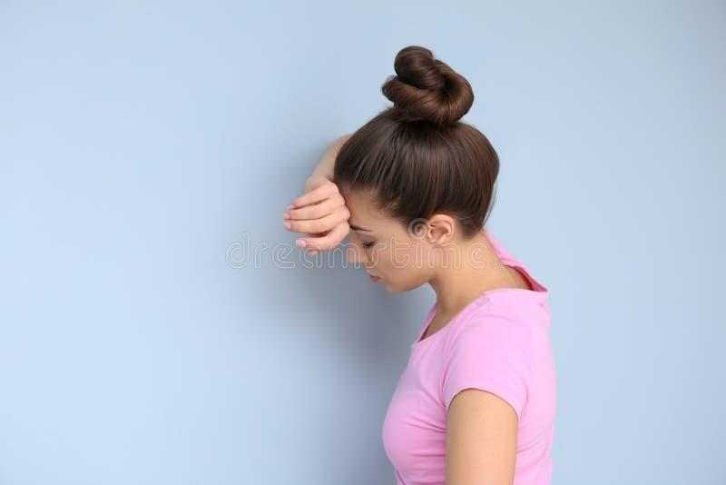 Sofferenza della donna dall'emicrania sul fondo di colore immagine stock libera da diritti