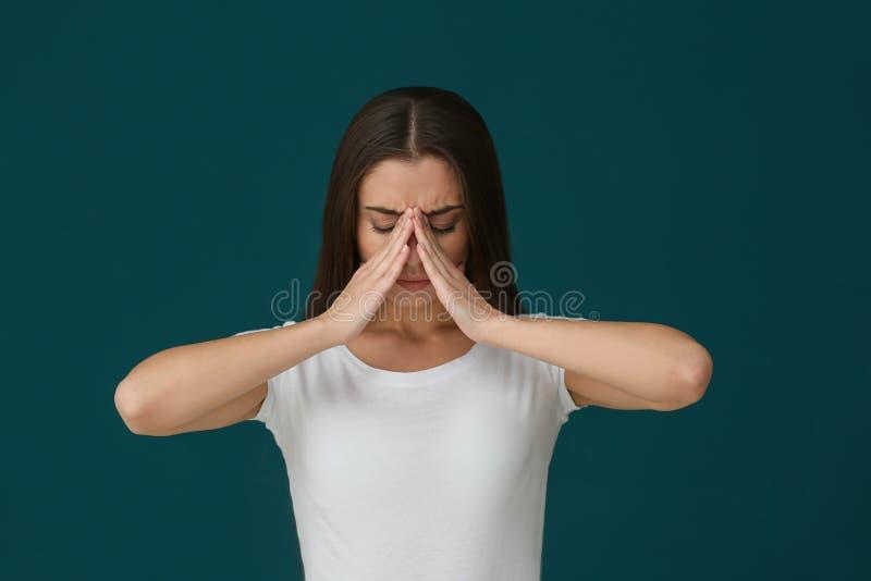 Sofferenza della donna dall'emicrania sul fondo di colore fotografie stock
