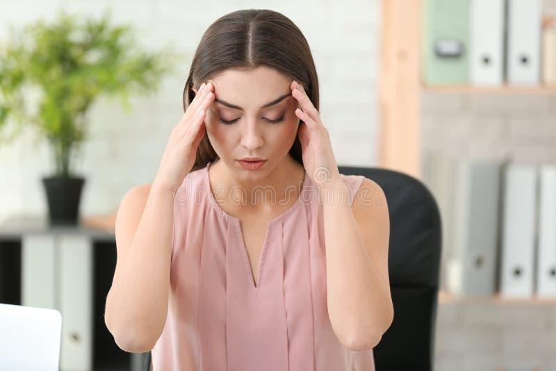 Sofferenza della donna dall'emicrania in ufficio fotografia stock