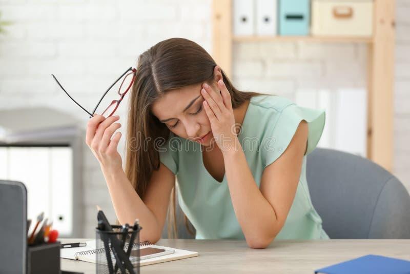 Sofferenza della donna dall'emicrania in ufficio fotografie stock libere da diritti