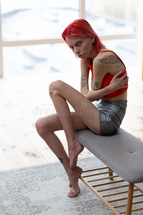 Sofferenza della donna dalla bulimia che si siede vicino alla finestra fotografie stock