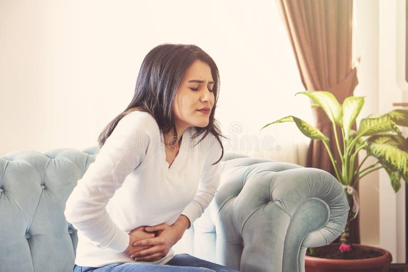 Sofferenza della giovane donna dal dolore addominale a casa Concetto di ginecologia fotografia stock libera da diritti