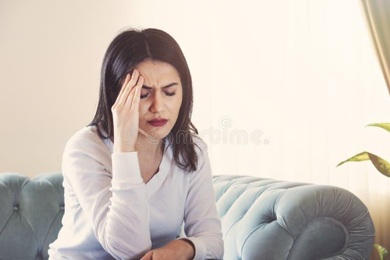 Sofferenza della giovane donna dall'emicrania forte o emicrania che si siedono a casa, intossicazione del tipo millenario e dolor fotografie stock libere da diritti