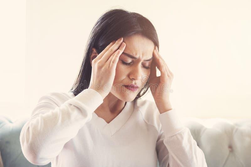 Sofferenza della giovane donna dall'emicrania forte o emicrania che si siedono a casa, intossicazione del tipo millenario e dolor fotografia stock
