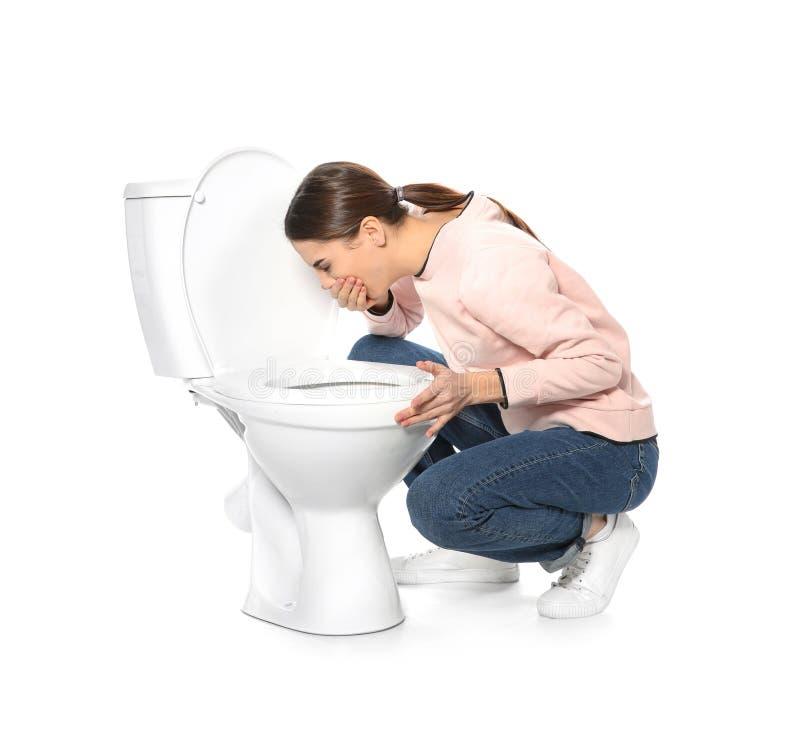 Sofferenza della giovane donna dalla nausea vicino alla ciotola di toilette immagine stock libera da diritti
