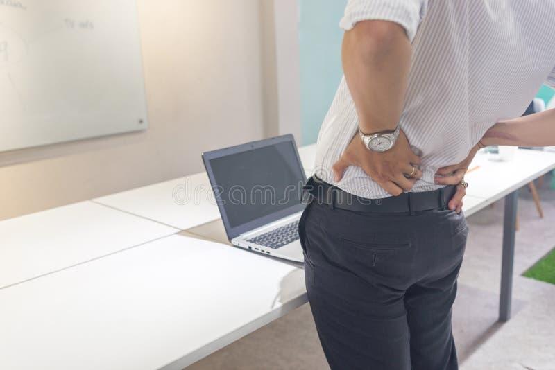 Sofferenza infelice dell'uomo d'affari dal mal di schiena alla sala riunioni fotografie stock