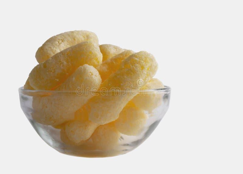 Soffi del cereale in una ciotola di vetro isolata su fondo bianco Spuntini soffiati aromatizzati croccanti Il partito, film fa un fotografie stock