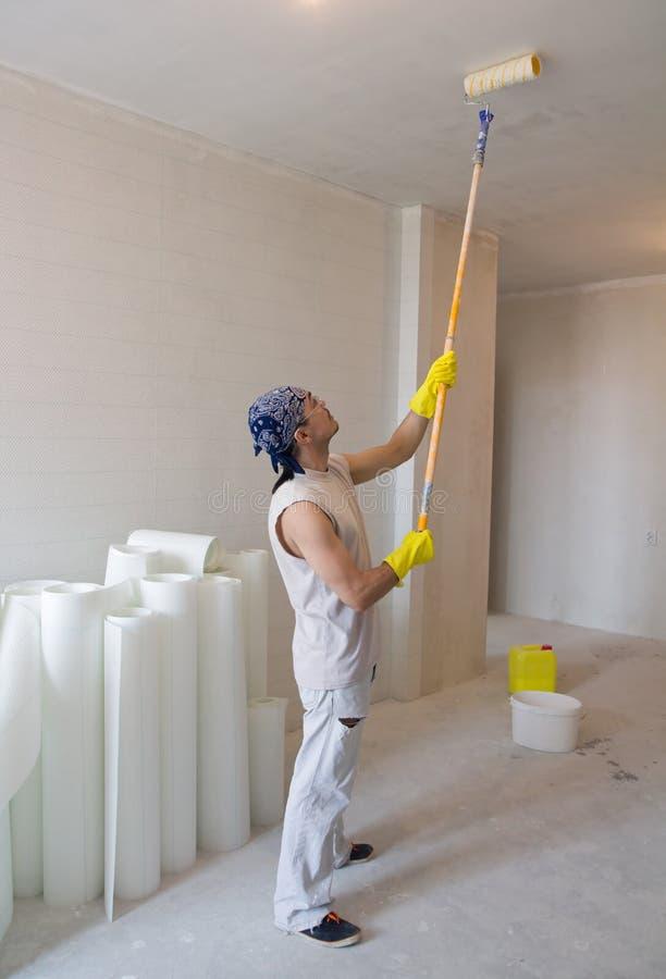 Soffitto della pittura del lavoratore con il rullo di pittura fotografie stock