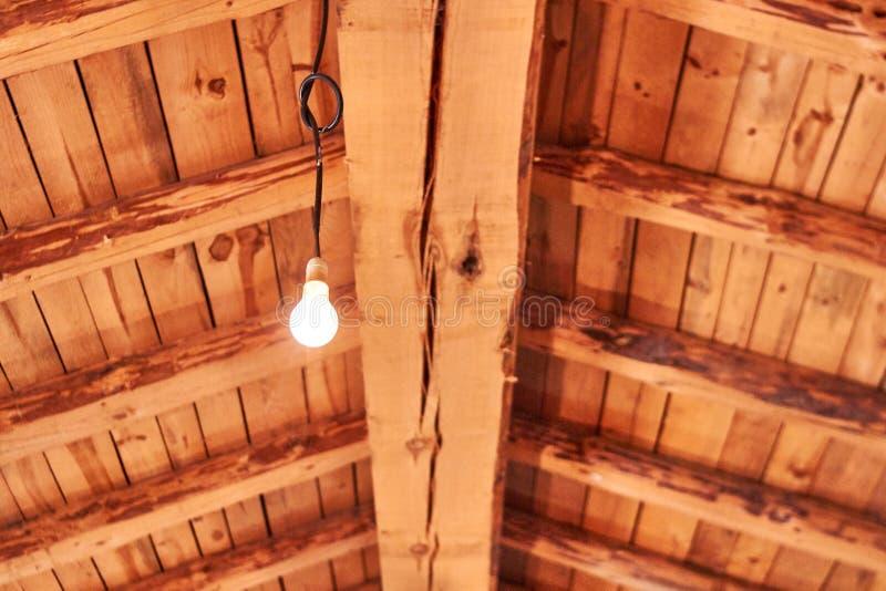 Soffitto di legno arancio con la lampadina immagine stock