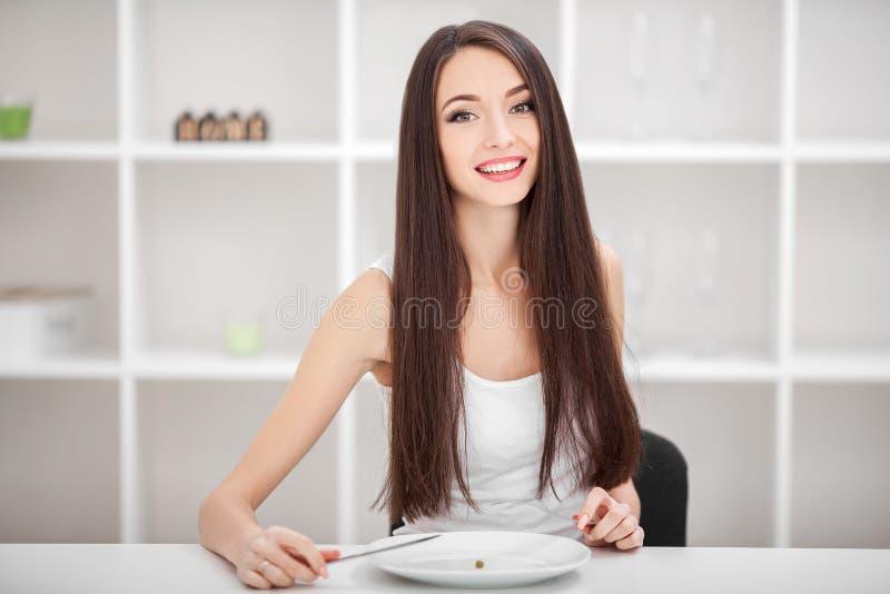 Soffrendo dall'anoressia Immagine della ragazza che prova a mettere un pisello su Th fotografie stock