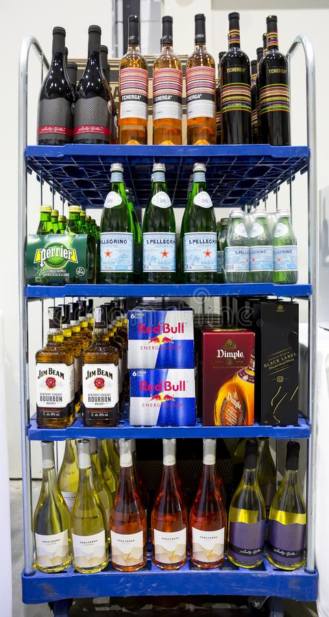 Alcohol bottles on a shelf. Sofia, Bulgaria - 19 December 2018: Alcohol bottles, water and energy drink on a shelf - Red Bull, Jim Beam, Dimple, Johnnie Walker stock image