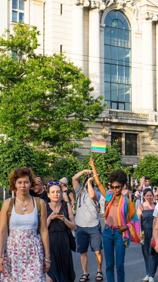 Sofia / Bulgaria - 10 June 2019: Black woman with afro hair in the pride parade of Sofia with a rainbow flag in her arm royalty free stock image