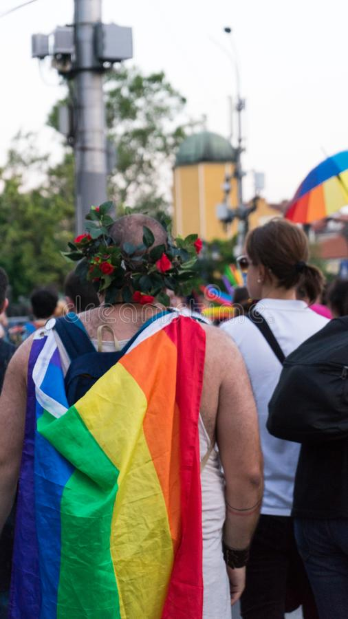 Sofia / Bulgaria - 10 June 2019: Fat guy with Rainbow Flag in the back and Crown of flowers supporting Sofia Pride walking in the stock images