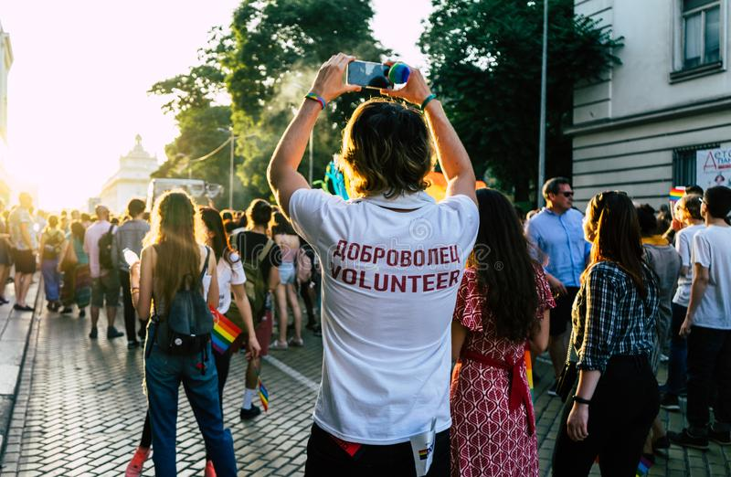 Sofia/Bulgarien - 10 Juni 2019: Volunter i Sofia Pride, LGBT ståtar i marschen Ställa upp som frivillig ta bilden med smartphonen arkivbild