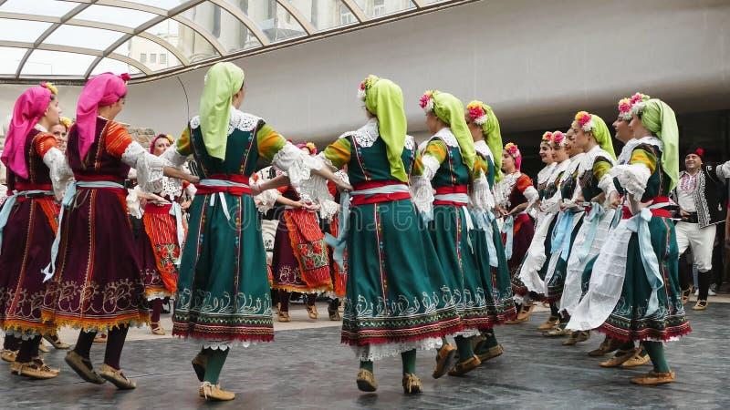 SOFIA BULGARIEN - MAJ 7, 2018: Folket i traditionella dräkter dansar bulgarian horo i Sofia, Bulgarien arkivfoton