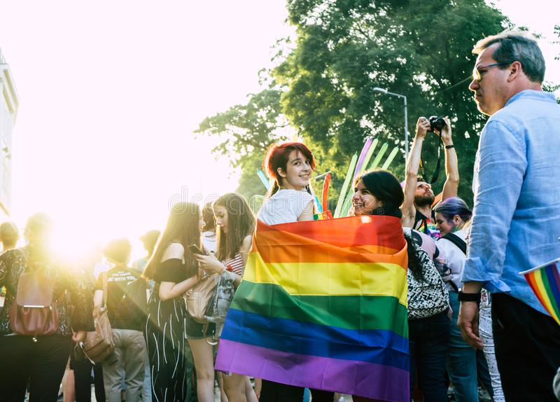 Sofia/Bulgarije - 10 Juni 2019: meisjes binnen van een grote regenboogvlag in de de ondersteunende homosexuelen en lesbiennes van royalty-vrije stock afbeelding