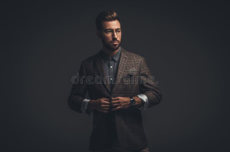 Sofistikerad stilig man i dräkt och exponeringsglas som justerar hans omslag, royaltyfri bild
