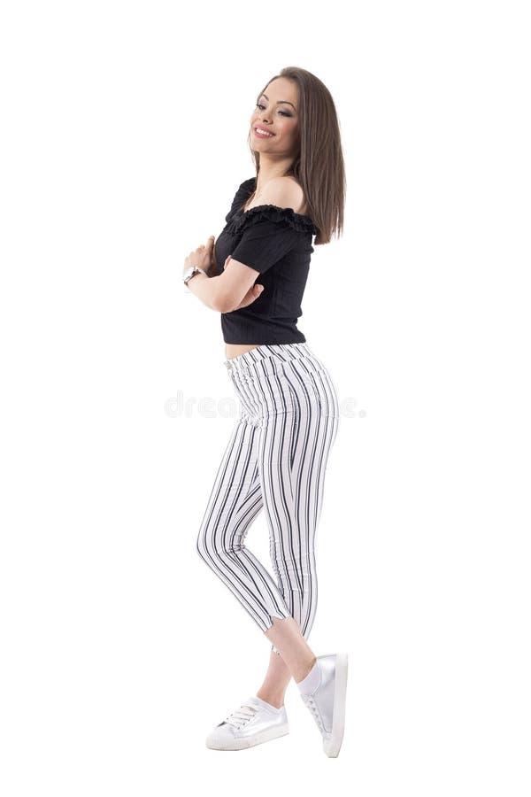 Sofistikerad ung härlig flicka med korsade armar som bort ler och ser fotografering för bildbyråer