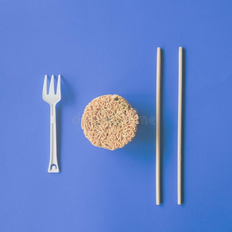 Sofortige Nudeln lokalisiert auf blauem Hintergrund eßstäbchen stockfotografie