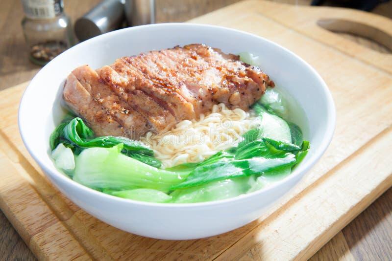 Sofortige Nudeln mit gebratenem Schweinefleisch-Kotelett mit Pak Choy oder Chinesen lizenzfreie stockfotografie