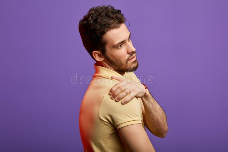 Sofrimento atrativo do homem da dor em seu ombro fotografia de stock