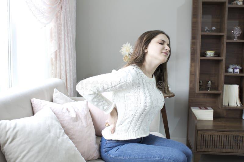 Sofrimento bonito da jovem mulher da dor lombar em casa imagens de stock royalty free