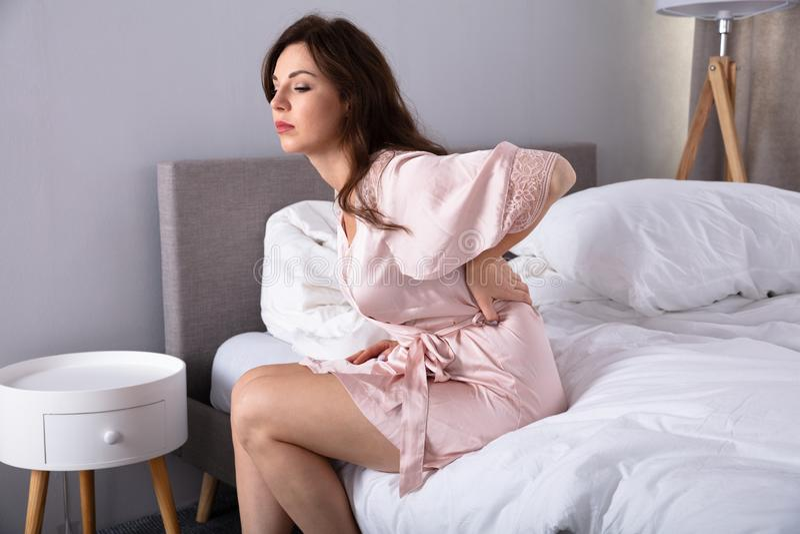 Sofrimento bonito da mulher da dor nas costas foto de stock
